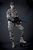 Woman Soldier. Beautiful young woman dressed in grey digital camouflage holding automatic rifle in her hands Royalty Free Stock Image