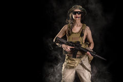 Woman soldier with assault rifle. Sexy woman soldier with an assault rifle on a black background Royalty Free Stock Photos
