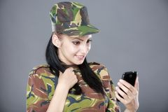 Woman soldier looks at a mobile phone Royalty Free Stock Photos