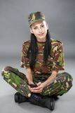 Woman soldier looks at a mobile phone Stock Photography