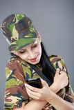 Woman soldier looks at a mobile phone Royalty Free Stock Photography