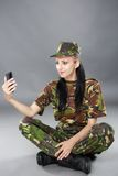 Woman soldier looks at a mobile phone Royalty Free Stock Images