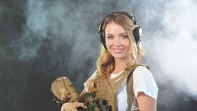 Armed woman soldier in military camouflage uniform protected with headphones. Woman soldier in military camouflage uniform protected with headphones, body armour stock video