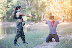 Woman soldier with a pistol arrested the culprit. Beside the reservoir stock photos