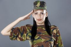 Woman soldier saluting isolated on gray background. Woman army soldier saluting isolated on gray background Stock Photography
