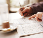 Woman solving Sudoku Stock Photography