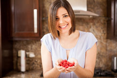 Woman with some raspberries. Beautiful young Hispanic woman holding a bunch of raspberries in her hands and smiling Stock Photo
