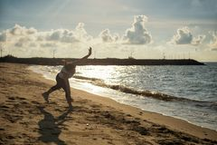 Woman somersault on sand beach. Young Asian athlete woman in running outfit suit somersault on sand beach during sunrise in early morning, Rayong, Thailand royalty free stock images