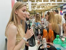 Kyiv Wine Festival by Good Wine in Ukraine. Woman sommelier pours white sparkling wine at Kyiv Wine Festival booth. 77 winemakers from around the world took royalty free stock photos