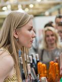 Kyiv Wine Festival by Good Wine in Ukraine. Woman sommelier presents sparkling wine at Kyiv Wine Festival booth. 77 winemakers from around the world took part Stock Image