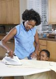 Woman With Son Ironing Clothes At Home Royalty Free Stock Images