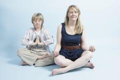 Woman and son meditating stock photos