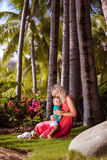 Woman with son. Woman in red dress sitting on green meadow under the palm trees and hugging her little son Stock Photography