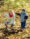 Woman with  son resetting  tree in autumn Stock Photo