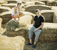 Woman with the son are sitting on the haystack Stock Image