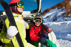 Woman and son in skiing suits sitting on car trunk Royalty Free Stock Photography
