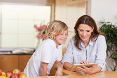 Woman and son using tablet in the kitchen Stock Image