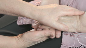 Woman soothes elderly woman during stress. Woman holding a flabby wrinkled hands of an old woman. She soothes the old woman in times of stress stock footage