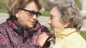 Woman soothes old woman during stress outdoors. Adult woman soothes old woman aged 80s during stress outdoors stock video footage