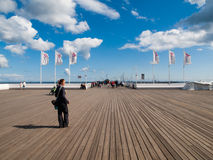 Woman on Sopot pier. SOPOT, POLAND - CIRCA 2014: The Sopot Pier is the longest wooden pier in Europe, 511 m. Taken on sunny end of summer day circa 2014 in Sopot Stock Photo