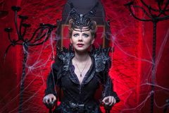 Woman in a sorceress costume. Sits on a throne in a red room Royalty Free Stock Photo