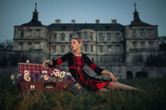 Woman sorceress next to suitcase with flowers on background of ancient castle. Stock Photo