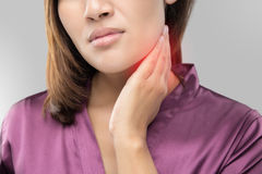 Woman with a sore throat holding her neck stock photos