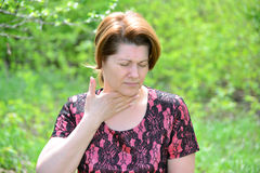 Woman with sore throat in nature Stock Image