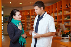 Woman with sore throat in pharmacy. Women with sore throat in pharmacy talking to pharmacist Royalty Free Stock Photography