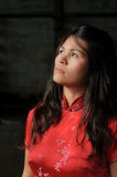 Woman in sorrow. Portrait of a beautiful asian woman, wearing a red chinese dress. She's looking up into the light with a pensive expression, as in sorrow or royalty free stock photos