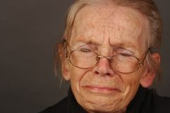 Woman with Sorrow. Image of Elderly woman with sorrow on Grey Stock Photo