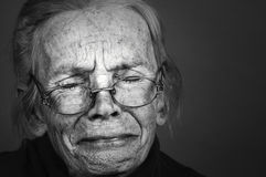 Woman with Sorrow. Image of Elderly woman with sorrow on Grey Royalty Free Stock Photos