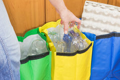 Woman is sorting household waste. Female hand is sorting plastic to the yellow bag. Household Waste concept royalty free stock photo
