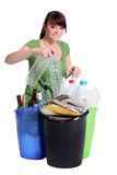 Woman sorting recycling. Into different bins royalty free stock photography