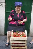 A woman sorting vegetables in front of green door in Amalfi, a town in the province of Salerno, in the region of Campania, Italy,  Royalty Free Stock Image