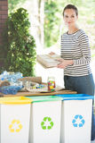 Woman sorting waste everyday. Young woman sorting waste everyday, putting paper waste to correct bin. Recycling concept stock image