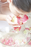Woman at spa. Young woman at spa washing her face with rose petals water royalty free stock images