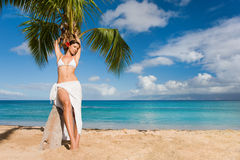 Woman spa beauty beach. Woman on beach with palm tree wearing white tropical sarong with flower in maui, hawaii Royalty Free Stock Photo