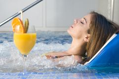 Woman in a spa bed relaxing. With orange juice royalty free stock photos