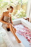 Woman Spa Body Care Treatment. Flower Rose Bath. Beauty, Skincar. Woman Spa Body Care Treatment. Beautiful Blonde Girl In Towel Sitting Near Flower Rose Bath In royalty free stock photo