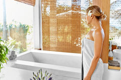 Woman Spa Body Care Treatment. Flower Rose Bath. Beauty, Skincare. Woman Spa Body Care Treatment. Beautiful Blonde Female In Towel Going To Take Flower Bath In royalty free stock images