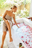 Woman Spa Body Care Treatment. Flower Rose Bath. Beauty, Skincare. Woman Spa Body Care Treatment. Beautiful Blonde Girl In Towel Sitting Near Flower Rose Bath In stock images