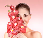 Woman at spa. Closeup portrait of beautiful woman with red orchid flowers  on pink background, enjoying day spa, beauty treatment concept Royalty Free Stock Images