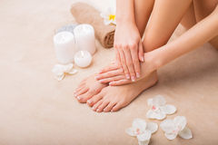 Woman at spa with done manicure and pedicure stock photography