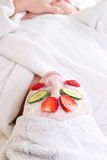 A woman at the spa with a faci. Al mask, cucumber and strawberries Royalty Free Stock Photography