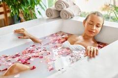 Woman Spa Flower Bath. Aromatherapy. Relaxing Rose Bathtub. Beauty Stock Photo