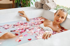 Woman Spa Flower Bath. Aromatherapy. Relaxing Rose Bathtub. Beauty royalty free stock photos