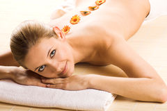 Woman in spa with flowers Stock Images
