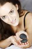 Woman with spa hot rocks. Attractive young woman holding spa treatment warm stones relaxing on a bed in black underwear Royalty Free Stock Photo