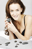 Woman with spa hot rocks. Attractive young woman holding spa treatment warm stones relaxing on a bed in black underwear Royalty Free Stock Photography